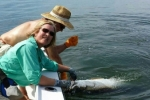 Debbie Miller poses with her catch while Bill Miller removes the hook for a release during the 2015 Suncoast Tarpon Roundup